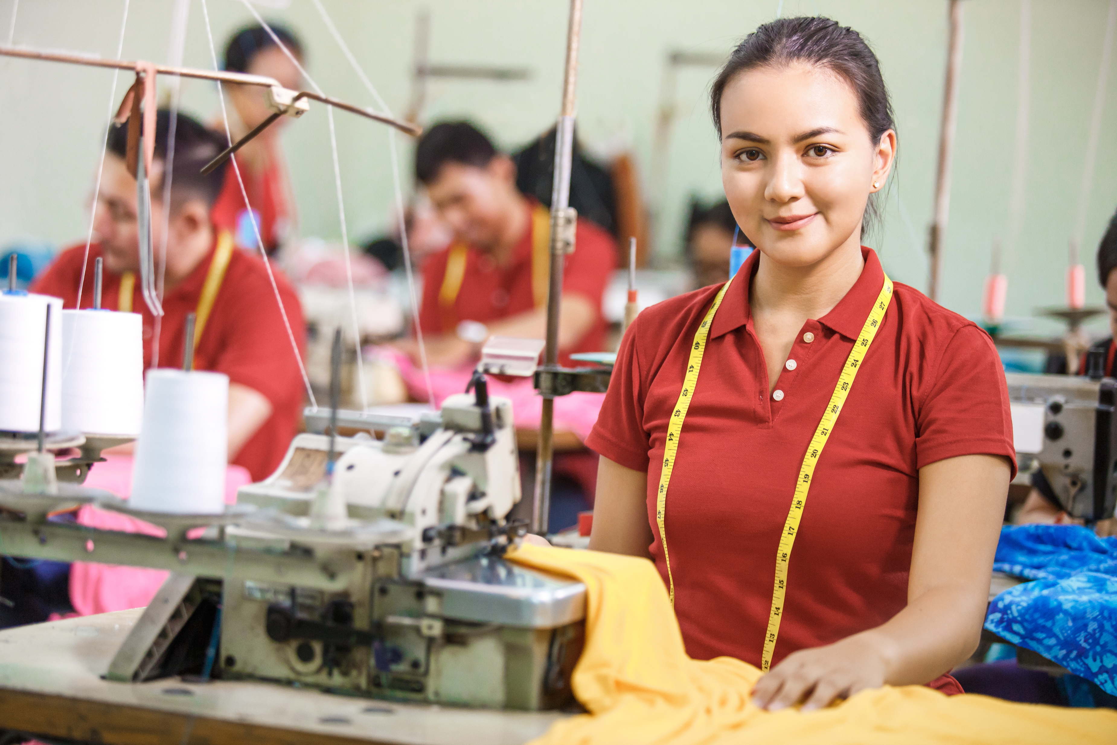 Seamstress in textile factory smiling whilst sewing