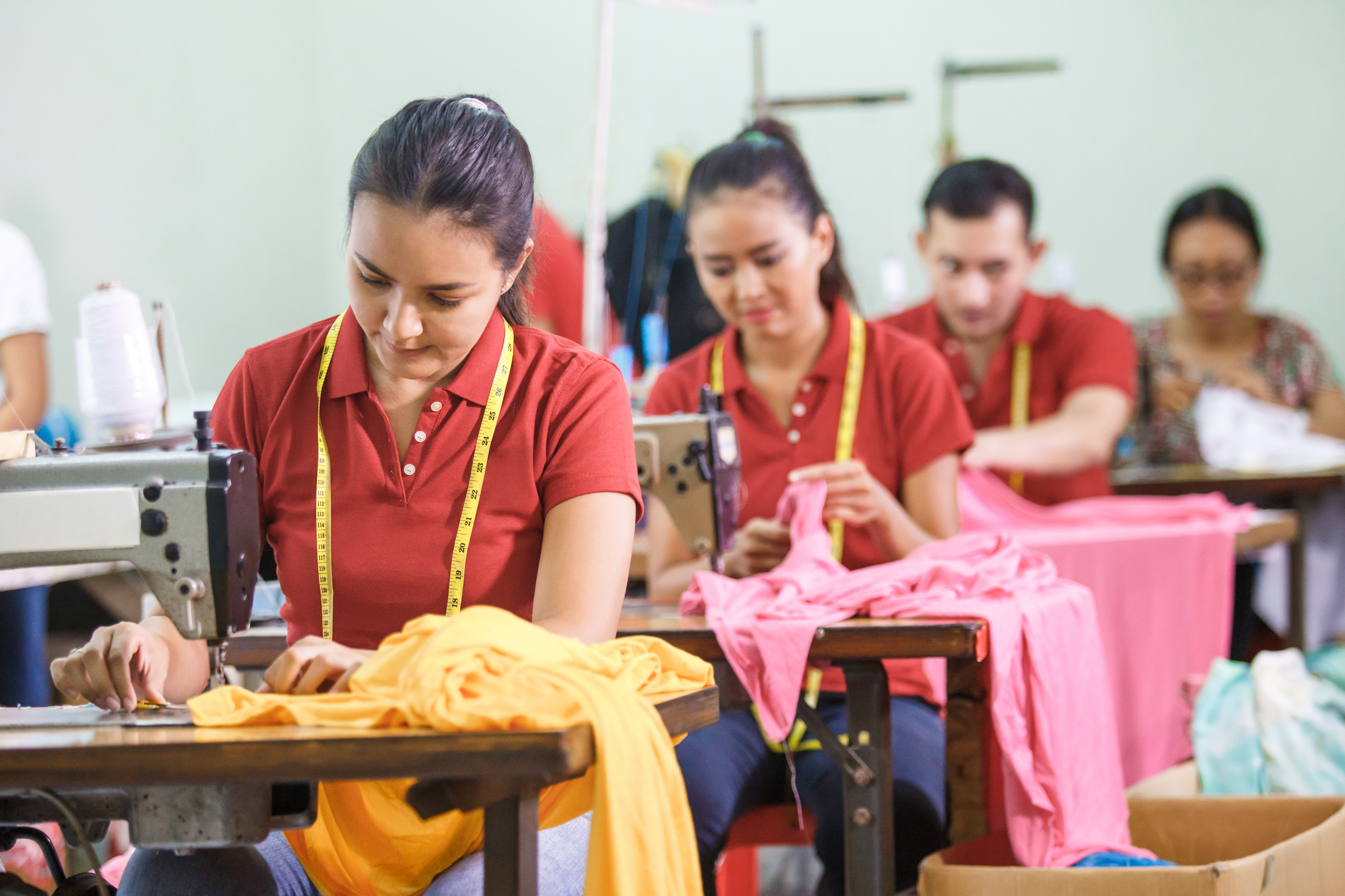 Workers in garment factory sewing with industrial sewing machine